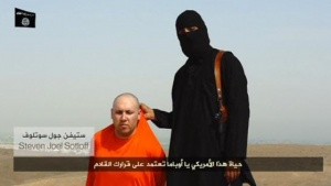A masked Islamic State militant speaks next to a man purported to be U.S. journalist Steven Sotloff at an unknown location in this still image from an undated second video posted on a social media website. REUTERS/SOCIAL MEDIA WEBSITE VIA REUTERS TV