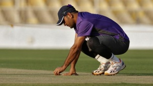 Mahendra Singh Dhoni inspects the pitch during a cricket practice session in Ahmedabad November 12, 2012. REUTERS/Amit Dave/Files