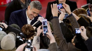 Director and actor George Clooney signs autographs as he arrives on the red carpet for the screening of the movie 'The Monuments Men' at the 64th Berlinale International Film Festival in Berlin February 8, 2014. REUTERS/Tim Brakemeier/Pool/Files