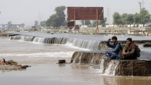 Flood victims sit by a damaged road as they look over floodwaters in Muzzafargarh, Punjab province September 15, 2014. REUTERS/Asim Tanveer