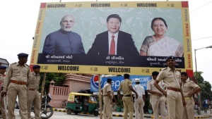 Police personnel stand guard in front of a boarding with images of (L-R) India's Prime Minister Narendra Modi, China's President Xi Jinping and Anandiben Patel, Chief Minister of Gujarat, ahead of Xi's arrival in Ahmedabad September 16, 2014. REUTERS/Amit Dave