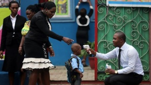 A school official takes a pupil's temperature using an infrared digital laser thermometer in front of the school premises, at the resumption of private schools, in Lagos September 22, 2014. REUTERS/Akintunde Akinleye
