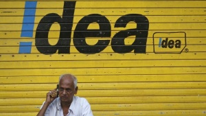 A man speaks on his mobile phone as he sits in front of a shop displaying the Idea Cellular Ltd's logo on its shutter in Mumbai April 28, 2014. REUTERS/Danish Siddiqui/Files