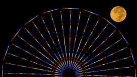 """The moon is pictured behind a ferris wheel on the pier in Santa Monica, California after a total lunar eclipse, also known as a """"blood moon,"""" October 8, 2014. REUTERS/Lucy Nicholson"""