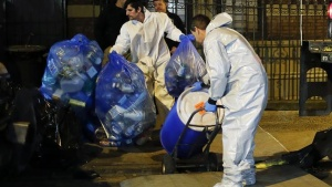 "Members of a cleaning crew with ""Bio Recovery Corporation"" wearing personal protective equipment (PPE) push a barrel to be loaded in a truck of Centers for Disease Control and Prevention (CDC) after cleaning the apartment where Dr. Craig Spencer lives in New York October 24, 2014.  REUTERS/Eduardo Munoz"