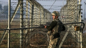 A Border Security Force (BSF) soldier patrols near the fenced border with Pakistan in Suchetgarh, southwest of Jammu January 11, 2013. REUTERS/Mukesh Gupta/Files