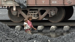 Children of labourers walk beside a railway track inside a coal yard on the outskirts of Ahmedabad August 20, 2010. REUTERS/Amit Dave/Files