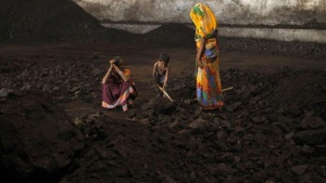 Labourers rest as a boy playfully shovels coal at a yard in Ahmedabad November 20, 2014. REUTERS/Amit Dave/Files