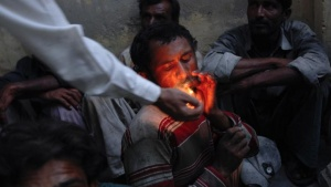 A policeman lights a cigarette for a fisherman from India amongst other fishermen held in a Karachi police station, after being detained in Pakistan waters, October 21, 2012. REUTERS/Akhtar Soomro/Files