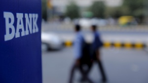 Commuters walk past a bank sign along a road in New Delhi, India, November 25, 2015. REUTERS/Anindito Mukherjee