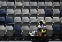 A lone spectator drinks water as she watches the first round match between Sloane Stephens of the U.S. and China's Wang Qiang at the Australian Open tennis tournament at Melbourne Park, Australia, January 18, 2016. REUTERS/Issei Kato