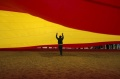 A child walks under a giant Spanish flag unfurled by supporters of Spain's Prime Minister Mariano Rajoy to support his candidacy for Spain's general election at Malagueta beach in Malaga, southern Spain, December 5, 2015. REUTERS/Jon Nazca