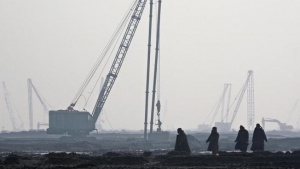Labourers walk near the land filling area at the new Caofeidian iron ore port on the northeastern coast of China's Hebei province January 23, 2007. REUTERS/Reinhard Krause (CHINA)