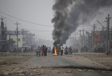 Protesters stand near burning tyres as they gather to block the highway connecting Nepal and India, during a general strike called by Madhesi protesters demonstrating against the new constitution in Birgunj, Nepal November 5, 2015. REUTERS/Navesh Chitrakar/Files