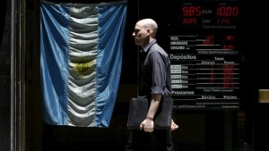 A man walks past a currency exchange rates board at a money exchange in Buenos Aires' financial district, Argentina, December 16, 2015. REUTERS/Marcos Brindicci