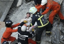 Rescue personnel help a child rescued at the site where a 17-storey apartment building collapsed during an earthquake in Tainan, southern Taiwan, February 6, 2016. REUTERS/Stringer