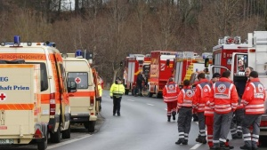 Cars of firefighters and ambulances are parked along a road near Bad Aibling in southwestern Germany, February 9, 2016. REUTERS/Michael Dalder