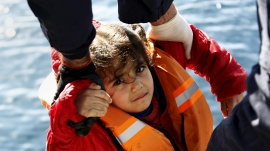 Greek Coast Guard officers move a girl from a dinghy carrying refugees and migrants aboard the Ayios Efstratios Coast Guard vessel, during a rescue operation at open sea between the Turkish coast and the Greek island of Lesbos, February 8, 2016. REUTERS/Giorgos Moutafis