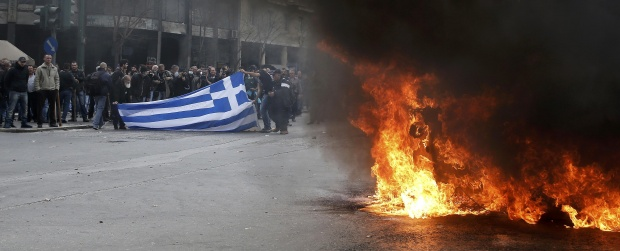 Greek farmers hold a Greek national flag near a burning garbage container during a protest against planned pension reforms outside the Agriculture ministry in Athens, Greece, February 12, 2016.      REUTERS/Alkis Konstantinidis