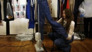 A woman steams a pair of jeans backstage before the Levi's Fall/Winter 2012 collection show during New York Fashion Week February 15, 2012. REUTERS/Allison Joyce