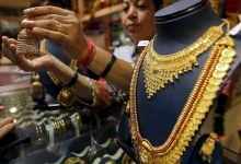 A saleswoman shows a gold earring to customers at a jewellery showroom in Mumbai, India, July 21, 2015. REUTERS/Shailesh Andrade/Files