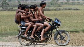 Boys ride a motorbike on their way back home after taking a bath in a canal at Chachura village, in Uttar Pradesh April 4, 2012. REUTERS/Parivartan Sharma/Files