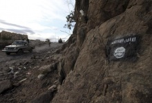 Shi'ite Houthi rebels drive a patrol truck past an Ansar al-Sharia flag painted on the side of a hill, along a road in Almnash, the main stronghold of Ansar al-Sharia, the local wing of Al Qaeda in the Arabian Peninsula (AQAP) in Rada, Yemen November 22, 2014. REUTERS/Mohamed al-Sayaghi
