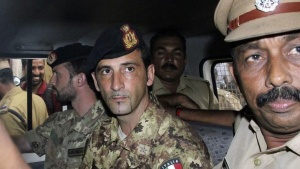 Salvatore Girone (centre L) and Latorre Massimiliano (3rd R), members of the navy security team of Napoli registered Italian merchant vessel Enrica Lexie, sit in a police vehicle after they appeared before a court at Kollam in Kerala March 5, 2012. REUTERS/Sivaram V/Files