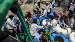 Residents hold plastic hoses as they fetch water from a government-run water tanker in Masurdi village, in Latur, India, April 16, 2016. REUTERS/Danish Siddiqui/Files