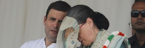 Congress party president Sonia Gandhi wipes her sweat as party's vice-president Rahul Gandhi (L) watches during a farmers rally at Ramlila ground in New Delhi, India, September 20, 2015. REUTERS/Adnan Abidi/Files