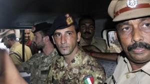 Salvatore Girone (centre L) and Latorre Massimiliano (3rd R), members of the navy security team of Napoli registered Italian merchant vessel Enrica Lexie, sit in a police vehicle after they appeared before a court at Kollam in Kerala March 5, 2012. REUTERS/Stringer/Files