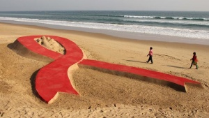 People walk near a red ribbon sand sculpture created by Indian sand artist Sudarshan Patnaik on the eve of World AIDS Day on a beach in the eastern Indian state of Odisha November 30, 2012. REUTERS/Stringer/files