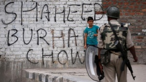 A boy stands next to a wall painted with graffiti as an Indian policeman stands guard during a protest in Srinagar against the recent killings in Kashmir, July 22, 2016. REUTERS/Danish Ismail