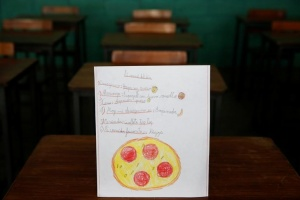 """A drawing made during a lesson at a school shows what a student ate during the course of a day in Caracas, Venezuela July 14, 2016. The student wrote, """"Ate corn cake with cheese for breakfast; had spaghetti with egg for lunch and a cookie for dinner."""" The student said that pizza was their favourite dish. REUTERS/Carlos Jasso"""