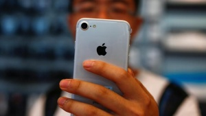 A man holds his new iPhone 7 at an Apple store in Beijing, China, September 16, 2016.  REUTERS/Thomas Peter