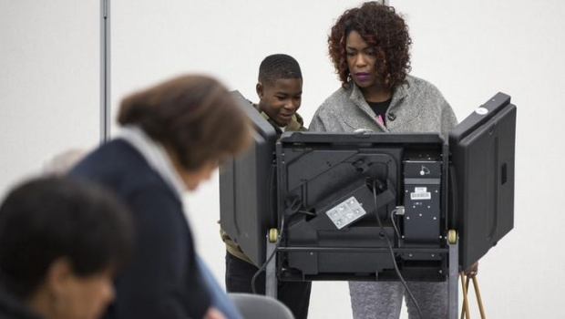 Jordan Williams, 10, looks on as his mother, Pamela Williams, casts her ballot in the U.S. midterm elections in Ferguson, Missouri November 4, 2014. REUTERS/Whitney Curtis