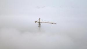 A crane is seen among thick fog in Yantai, Shandong province, China, October 19, 2016. China Daily/via REUTERS