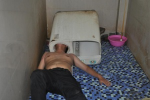 A man lies on the floor with his head stuck in a washing machine in Fuzhou, China May 29, 2016. According to local media, the man was trying to figure out why the machine was not working when his head became trapped. Firefighters eventually cut the machine and saved him. REUTERS/Stringer
