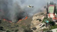 Wind-driven brush fire threatens California homes