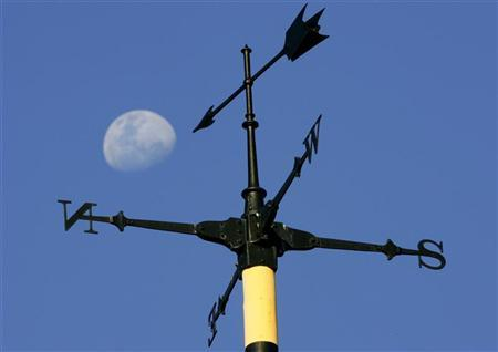 The moon rises over a weather vane on a sunny winter day in Sydney August 16, 2005. Joe Bastardi, whose title at the Accuweather meteorological service is ''expert senior forecaster,'' has made hurricane and long-range temperature forecasts that have moved the U.S. energy markets for more than five years, making him a minor celebrity among traders. NTRES REUTERS/Tim Wimborne