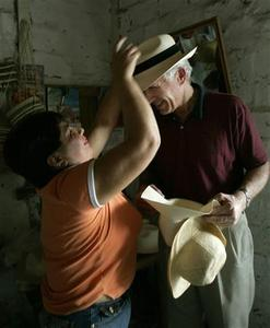 Magdalena Pachay fits a Panama hat on an English tourist in Montecristi, a coastal village in the Province of Manabi in this photo taken January 8, 2007. Ecuadoreans have mostly swallowed their chagrin and accepted that their most famous export will for evermore be known as the ''Panama hat''. REUTERS/Guillermo Granja