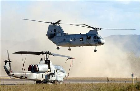 A United States Marine Corps CH46 Sea Knight heavy lift helicopter flies over a Cobra attack gunship during war games with the United States at Shoalwater Bay in this file photo from September 19, 2003. The U.S. military confirmed on Wednesday that a transport helicopter, similar to the Sea Knight seen here, had come down near Baghdad but declined to comment on any casualties. REUTERS/Australian Defence Force/Jodie Richter WB/RCS