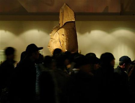 Visitors surround a two-meter-tall stone statue of Akhenaten at the National Museum of China in Beijing December 5, 2003. Dutch archaeologists have discovered the tomb of the Pharaoh Akhenaten's seal bearer, decorated with paintings including scenes of monkeys picking and eating fruit, Egyptian antiquities officials said on Wednesday. REUTERS/Andrew Wong