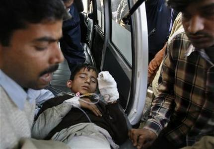 Rescue workers carry a boy, injured in blasts on the Samjhauta Express train, at a hospital in New Delhi, February 19, 2007. REUTERS/Adnan Abidi