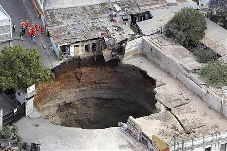A giant sinkhole that swallowed several homes is seen in Guatemala City February 23, 2007. REUTERS/Stringer