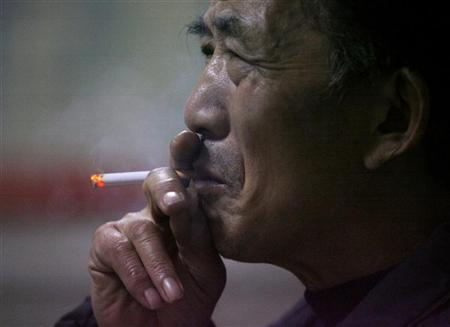 An elderly man smokes his cigarette at a stock exchange in Nanjing, east China's Jiangsu province in this January 4, 2007 file photo. China's stability could be threatened if the government tried to curb smoking, a senior official said on Wednesday at a discussion of the annual meeting of parliament. REUTERS/Sean Yong (CHINA)