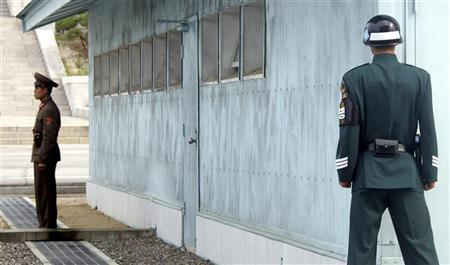 A South Korean soldier (R) looks at a North Korean soldier standing guard behind a concrete border in the truce village of Panmunjom in the demilitarized zone separating the two Koreas, in this November 1, 2006 file picture. A South Korean soldier may be a U.S. military deserter after he left his U.S. base and joined the South Korean army, apparently to avoid a tour of duty in Iraq, the defense ministry in Seoul said on Thursday. REUTERS/Lee Jae-Won