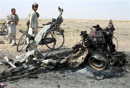 Afghans look at the wreckage at a suicide blast site in the southern Kandahar province March 17, 2007. One Afghan civilian was killed and three wounded on Saturday when a Taliban suicide bomber rammed an explosives-laden car into a NATO convoy, police said. REUTERS/Abdul Qahir