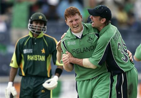 Ireland's Kevin O'Brien (C) is congratulated by team mate William Porterfield after Pakistan's Shoaib Malik (L) was caught behind during their World Cup cricket match in Kingston March 17, 2007. REUTERS/Andy Clark