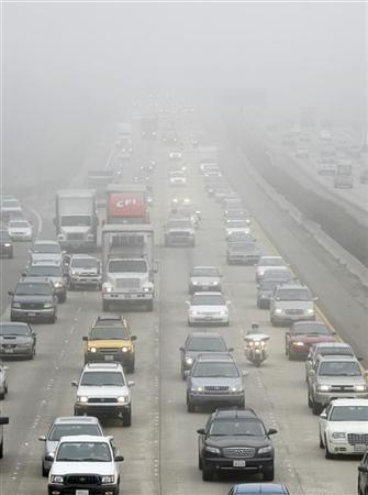 A California Highway Patrol officer travels south with commuters on Interstate 5 as they make their way through heavy morning fog near San Diego March 16, 2007. ''The United States must adopt a carbon emission control policy,'' John Deutch, head of the Central Intelligence Agency in 1995-96, said in a report released on Monday to the Trilateral Commission. REUTERS/Mike Blake